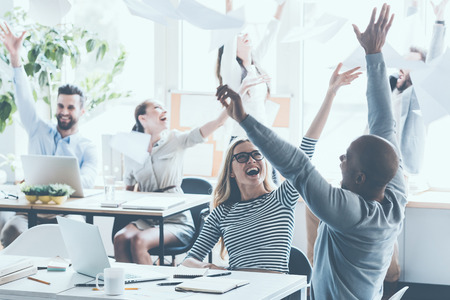 성공을 축하합니다. 젊은 비즈니스 사람들이 문서를 던지고 사무실에서 자신의 작업 장소에 앉아있는 동안 행복을 찾고 그룹