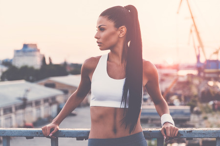 urban scene: Great day for training. Beautiful young woman in sports clothing looking away while standing on the bridge with evening sunlight and urban view in the background