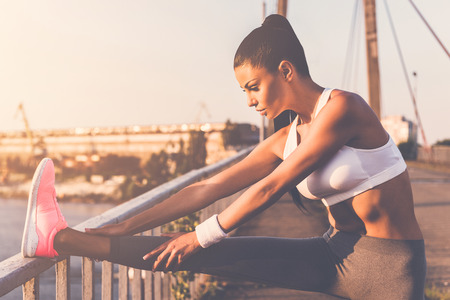 sports clothing: Stretching before jogging. Beautiful young woman in sports clothing doing stretching exercises while standing on the bridge Stock Photo