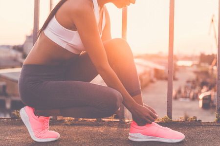 sports clothing: Preparing to run. Close-up of beautiful young woman in sports clothing tying her shoelaces while standing on the bridge with evening sunlight and urban view in the background Stock Photo