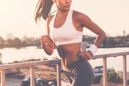 looking over shoulder: Evening jog. Close-up of beautiful young woman in sports clothing running along the bridge and looking over shoulder
