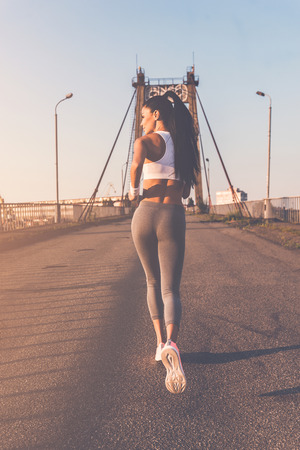moving activity: Getting fit. Full length rear view of beautiful young woman in sports clothing running along the bridge Stock Photo