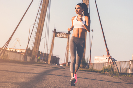 moving activity: Jogging is her life. Full length of beautiful young woman in sports clothing running along the bridge