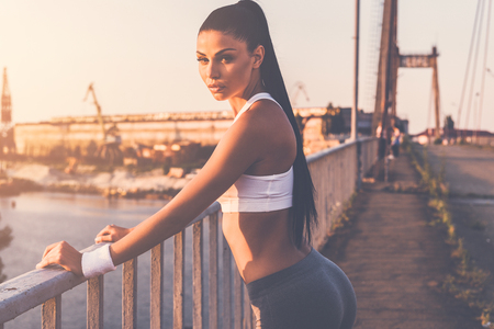 sports clothing: Sporty woman. Beautiful young woman in sports clothing looking at camera while standing on the bridge with urban view in the background