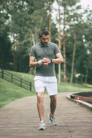 sports clothing: New great result! Full length of confident man in sports clothing looking at his wristwatch while walking in park