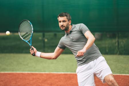 jugando tenis: tenista confianza. Seguro de joven en ropa deportiva jugar al tenis en la pista de tenis Foto de archivo