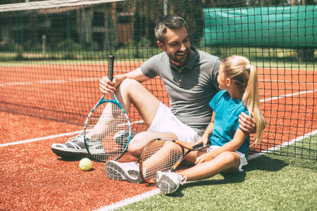 tennis net: Relaxing after good game. Cheerful father and daughter leaning at the tennis net and looking at each other with smiles while both sitting on tennis court