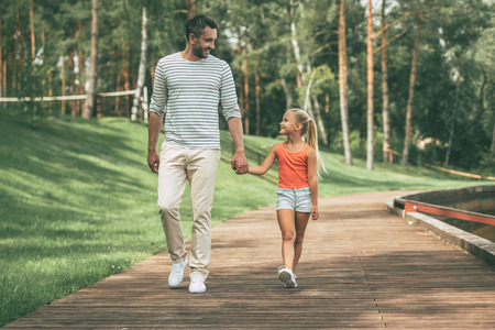 Enjoying great time with father. Front view of cheerful father and daughter holding hands and smiling while walking in park together
