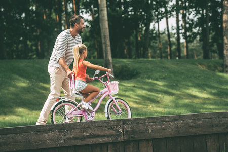 father daughter: Enjoying time with father. Side view of cheerful father teaching his daughter to ride a bicycle in park Stock Photo