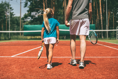 big game: Preparing to big game. Rear view of little blond hair girl in sports clothing carrying tennis racket and looking at her father walking near her by tennis court Stock Photo