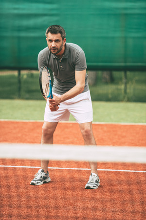 competitive sport: Practicing tennis. Confident young man in sports clothes carrying tennis racket and looking concentrated while standing on tennis court