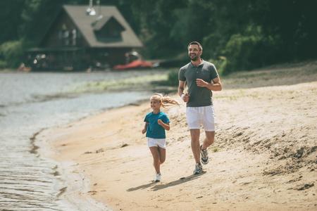 padre e hija: Deportivo como padre. Longitud total de padre e hija alegre en ropa deportiva a correr por la orilla del río junto Foto de archivo