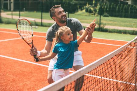 Tennis is leuk als vader in de buurt is. Vrolijke vader in sportkleding die zijn dochter onderwijzen om tennis te spelen terwijl allebei die zich op tennisbaan bevinden