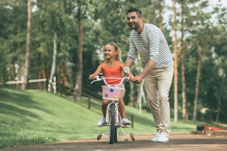 spending full: Spending quality time together. Full length of cheerful father teaching his daughter to ride a bicycle in park