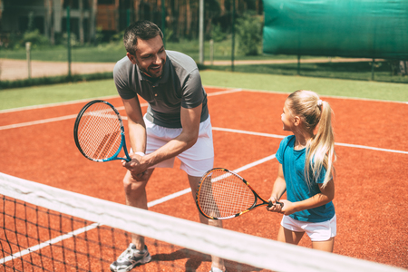 Practicing tennis. Cheerful father in sports clothing teaching his daughter to play tennis while both standing on tennis court Foto de archivo