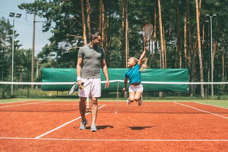 Petit vainqueur. pleine longueur de petite fille blonde de cheveux dans les vêtements de sport portant raquette de tennis et en regardant son père marchant près d'elle par un court de tennis