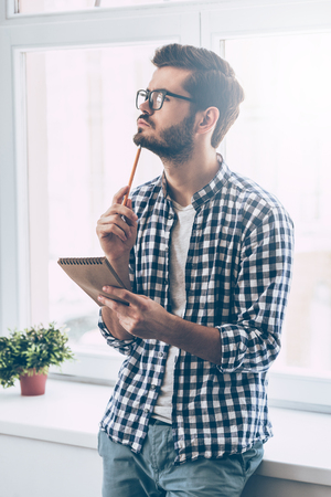 person writing: In search of inspiration. Thoughtful young man holding notebook and touching his chin with pencil while standing in front of the window Stock Photo