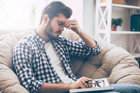 home keeping: Feeling tired. Frustrated young man holding book and massaging his nose while sitting in big chair at home and keeping eyes closed