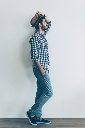metrosexual: Feeling casual. Full length side view of handsome young cheerful man holding one hand in pocket and adjusting his hat