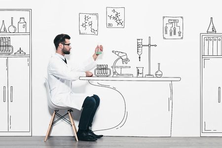 one man only: Scientific experiment. Confident young man in white uniform sitting against a wall and making scientific experiment in pencil drawn laboratory