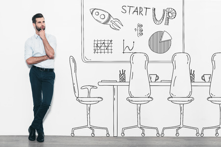 hand on chin: Dreaming about new business. Handsome young man in smart casual wear standing in front of the wall and near the pencil drawn office interior Stock Photo