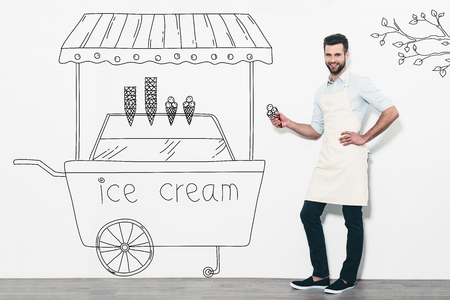 carretto gelati: Selling the best ice cream. Handsome young smiling man in apron standing in front of the white wall and near the pencil drawn ice cream cart