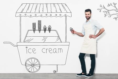 carretto gelati: Vendere il miglior gelato. Bel giovane sorridente in grembiule in piedi di fronte al muro bianco e vicino alla matita disegnato gelato carrello Archivio Fotografico