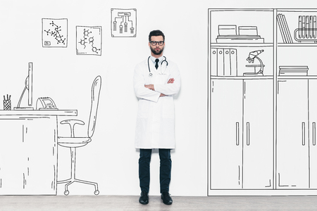 medical building: Confident doctor. Full length of confident young man in white uniform keeping arms crossed and looking at camera while standing against a wall with pencil drawn medical office Stock Photo