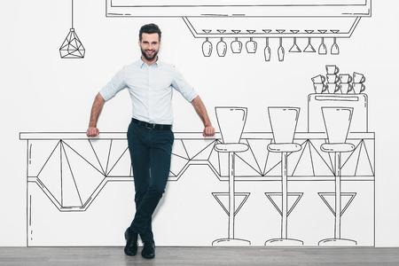 ice cream cart: Sognando nuovo business. Bel giovane uomo in piedi davanti alla parete e appoggiato alla matita disegnato gelato carrello Archivio Fotografico