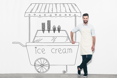 one man only: Dreaming about new business. Handsome young man in apron standing in front of the wall and leaning at the pencil drawn ice cream cart