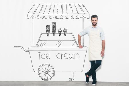 carretto gelati: Sognando nuovo business. Bel giovane uomo in grembiule in piedi di fronte al muro e appoggiato alla matita disegnato gelato carrello