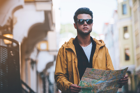 discovering: Discovering new places. Handsome young man holding map and looking away while standing on the city street