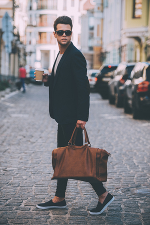 shoulder carrying: Handsome on the go. Full length of handsome young man in smart casual wear carrying bag and looking over shoulder while walking at the street