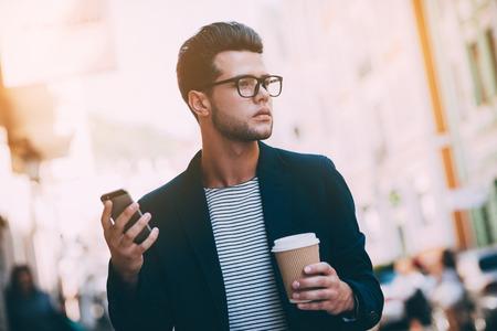 taza cafe: Vida en la ciudad. apuesto joven en ropa de sport elegante caminar por la calle, mientras que sostiene la taza de café y el teléfono inteligente