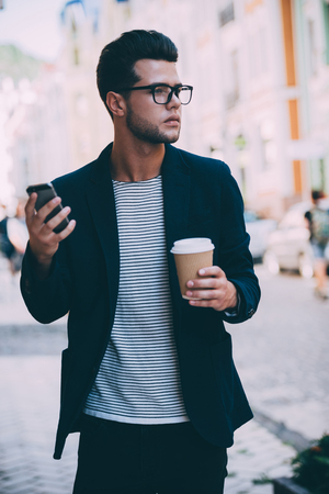 City lifestyle. Handsome young man in smart casual wear walking along the street while holding coffee cup and smart phone