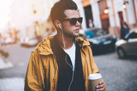 Enjoying city life. Handsome young man in headphones carrying coffee cup while walking along the city street Stock Photo