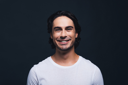 masculinity: Cheerful and handsome. Portrait of handsome young man looking at camera while standing against grey background Stock Photo