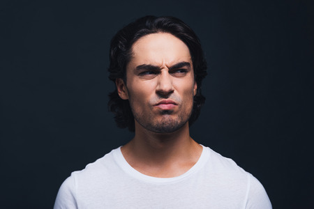 expressing: Making a face. Portrait of young man expressing disgust and looking away while standing against grey background