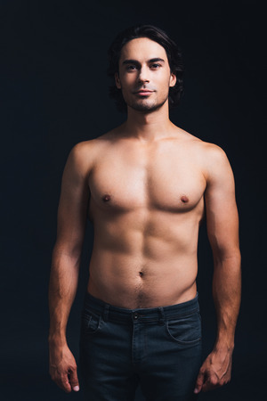 Charming handsome. Shirtless handsome man looking at camera while standing against black background Stock Photo