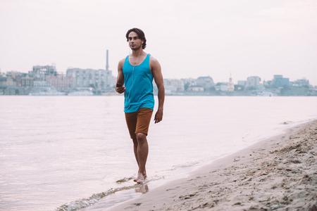 metrosexual: Enjoying nice evening. Full length of handsome young man in headphones walking along the riverside