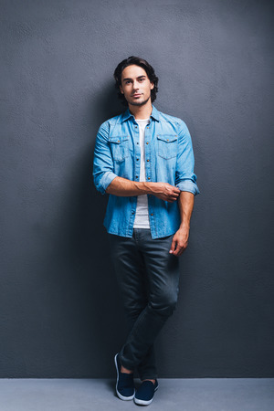 studio model: Stylish handsome. Full length of handsome young man looking at camera and adjusting sleeve of his jeans shirt while standing against grey background