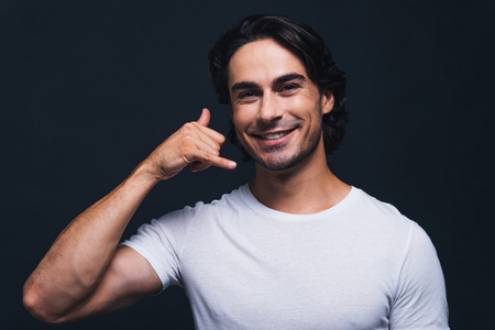 metrosexual: Call me! Handsome young smiling man looking at camera and gesturing mobile phone near face while standing against grey background Stock Photo