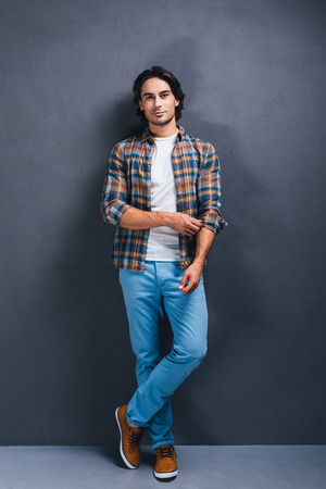 metrosexual: Casually handsome. Full length of handsome young man looking at camera and adjusting sleeve of his shirt while standing against grey background Stock Photo