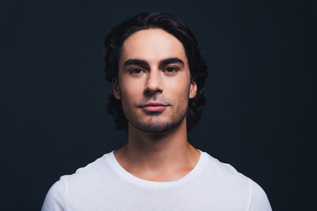 metrosexual: Young and handsome. Portrait of handsome young man looking at camera while standing against grey background