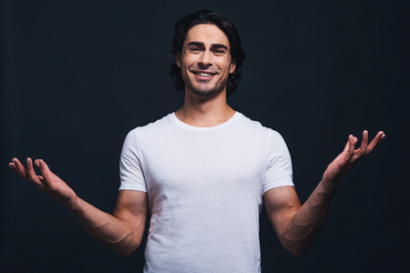 only man: Confident and handsome. Handsome young smiling man looking at camera and stretching out hands while standing against grey background