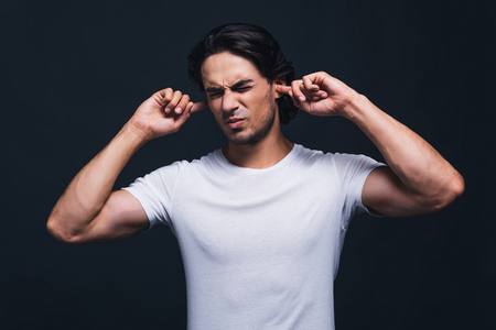 expressing negativity: This is too loud. Handsome young man expressing negativity and covering ears by hands while standing against grey background Stock Photo