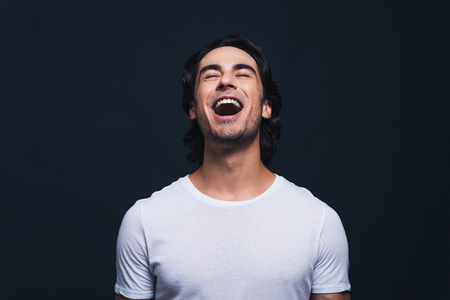 mouth  open: Feeling so happy. Portrait of happy young man keeping mouth open and eyes closed while standing against grey background