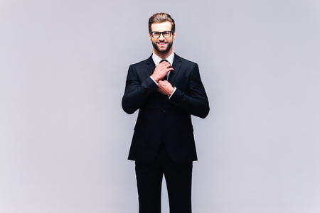 Confident and successful. Studio shot of handsome young man in full suit adjusting his necktie and looking at camera with smile