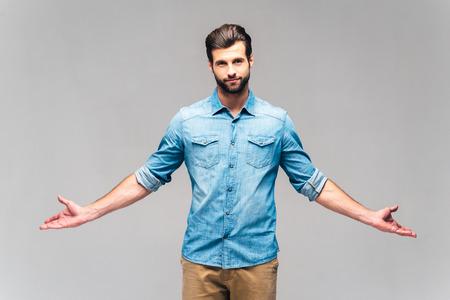 Immer wahr. Studio-Aufnahme von schönen jungen Mann in Freizeitkleidung in die Kamera und halten die Hände ausgestreckt Standard-Bild