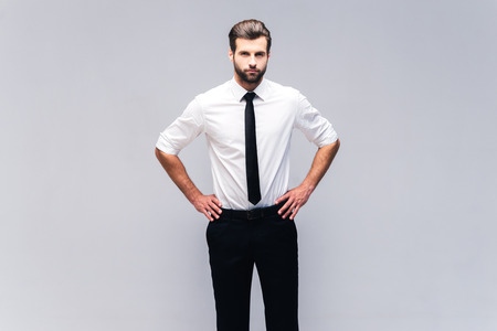 hands on hip: Young and confident. Studio shot of handsome young man in shirt and tie holding hands on hip and looking at camera